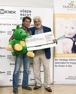 Mario Adorf üŸbergibt die Spende Ÿvon 20.000 EUR an Peter Maffay, Schirmherr der Tabaluga Kinderstiftung. Quelle: obs/Widex HšörgerŠäte GmbH